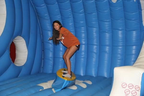 Texas girl balancing on surfboard simulator - Party Game Rental